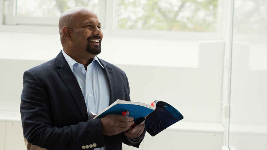 Man looking up from text book